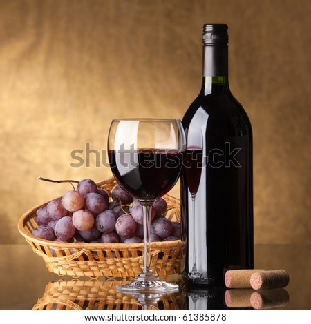 A bottle of red wine, glass and grapes on a golden background