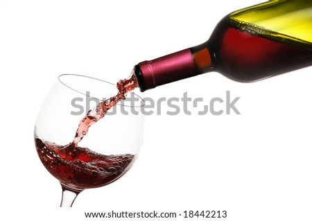 A bottle of red wine is being poured into a glass