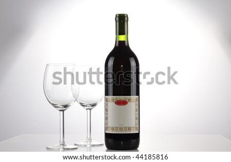 A bottle of red wine with a blank label and two emtpy wine glasses