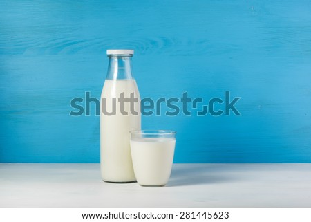 A bottle of rustic milk and glass of milk on a white table on a blue background, tasty, nutritious and healthy dairy products