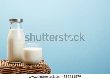 A bottle of rustic milk and glass of milk on wicker on a blue background, tasty, nutritious and healthy dairy products