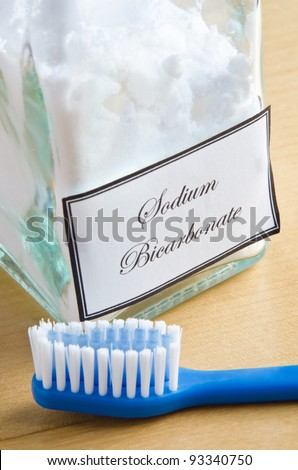 A bottle of sodium bicarbonate (baking soda) and a toothbrush on a wooden surface, to illustrate non-toxic dental care or natural toiletries.