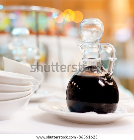 A bottle of soy sauce on a table/ Soy sauce in a bottle