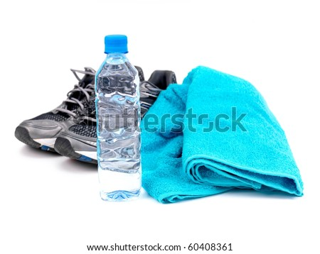 A bottle of water, joggers and a sports towel isolated against a white background