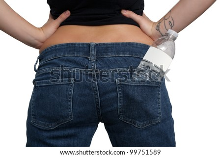 A bottle of water with a blank white label is tucked in the back pocket of the jeans of a young female.
