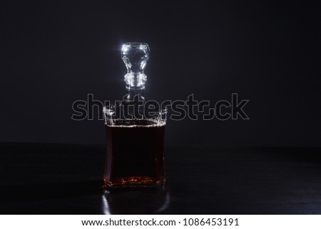 a bottle of whiskey,  or rum, or alcohol stands on a table on a dark background #1086453191