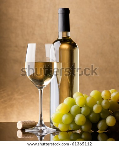 A bottle of white wine, glass and bunch of grapes on a golden background