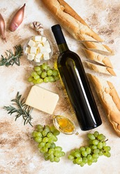 A bottle of white wine, grapes, cheese, butter, honey, baguette, shallot and rosemary. White wine and french cuisine concept. Flat lay, copy space, light marble background