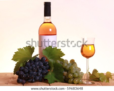 A bottle of white wine with grapes and leaves on wooden background. Focus on wineglass.