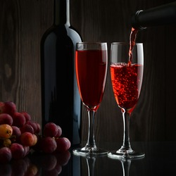 A bottle of wine, a bunch of ripe grapes and two glasses filled with red wine on a dark wooden background.