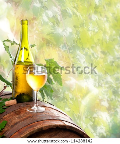 A bottle of wine and a glass of wine standing on an old wooden barrel. Against the background of the vine.