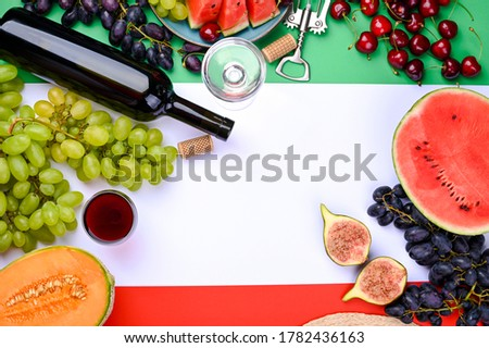 Photo of A bottle of wine, wineglass, grapes, different fruits and the flag of Italy. Country symbol backdrop. The concept of harvesting, august traditional summer vacation. Free space for text. Top view