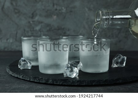A bottle with pouring vodka and shots of vodka on black tray Stock fotó ©