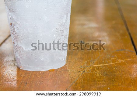 A bottom cup that have ice on left of orange-brown wood background