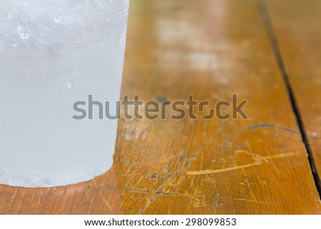 A bottom cup that have ice-water on left of orange-brown wood background