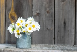 a bouquet of daisies in a metal mug stands on a wooden table, rustic style