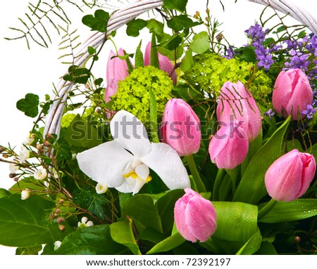a bouquet of flowers in a wicker basket in water drops on a white background