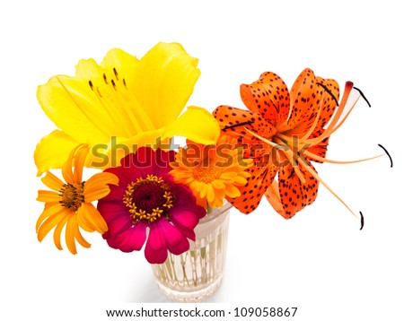 A bouquet of flowers of yellow lilies, daisies, and the leopard lily, in a glass vase. Isolated on white.