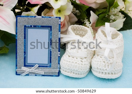 A bouquet of flowers with a pair of baby booties and an empty picture frame, Welcoming a baby