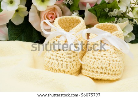 A bouquet of flowers with a pair of baby booties, yellow baby booties