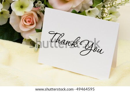A bouquet of flowers with a thank you card, thank you card