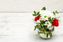 A bouquet of fresh flowers in glass vase. Valentine's day or Wedding concept. White old planks background, copy space
