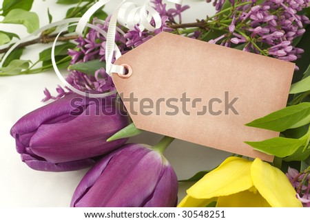 A bouquet of fresh spring tulips and lilac with a blank gift tag, horizontal with copy space