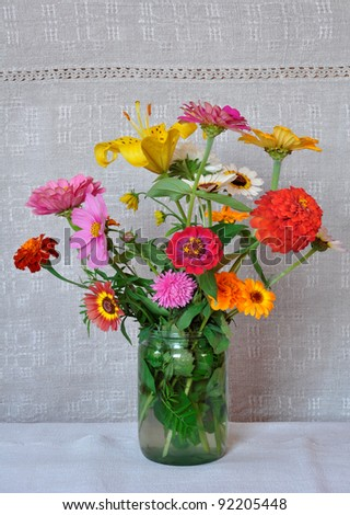 A bouquet of garden flowers in a glass jar on the background of an old linen canvas. August, the Central Russia
