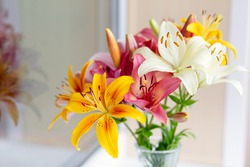 A bouquet of lilies in a vase in daylight