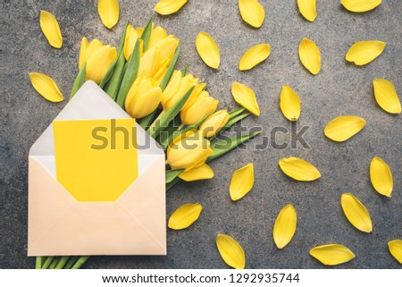 Photo of A bouquet of natural, fresh tulips in the composition with an open envelope. A protruding piece of paper ideal for writing. Romantic frame with flowers and vintage boards. Wedding or valentine day