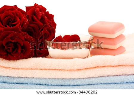 A bouquet of red roses and pink soap on towels