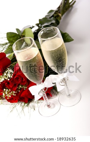 A bouquet of red roses and tow champagne flutes or toasting glasses with champagne on a white background