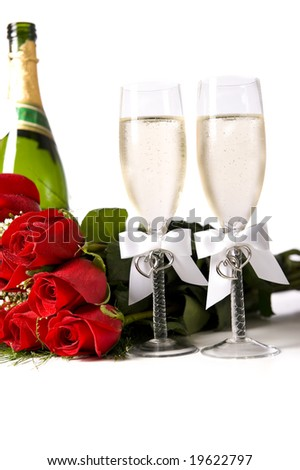 A bouquet of red roses and tow champagne flutes or toasting glasses with champagne on a white background - stock photo
