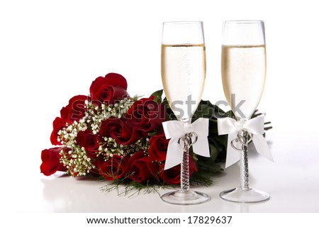 A bouquet of red roses and two champagne flutes or toasting glasses with champagne on a white background