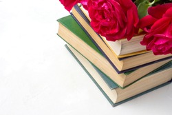 A bouquet of red roses on a pile of books on a light stone background. Concept love of literature and romance novels