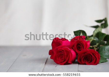 A bouquet of roses on the grey rustic wooden table