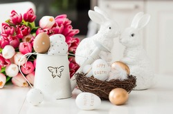 A bouquet of tulips, Easter bunnies and eggs with a golden pattern on the table. In the background is a white Scandinavian-style kitchen. Beautiful Easter greeting card. The minimal concept of Easter.
