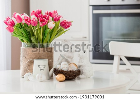 A bouquet of tulips, Easter bunnies and eggs with a golden pattern on the table. In the background is a white Scandinavian-style kitchen. Beautiful greeting card. The minimal concept.