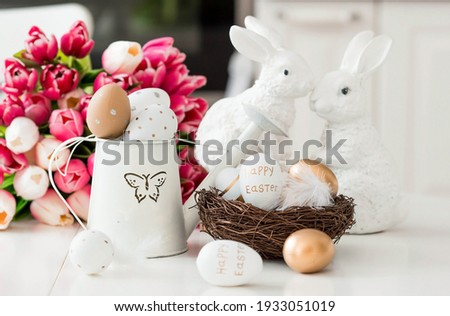 A bouquet of tulips, Easter bunnies and eggs with a golden pattern on the table. In the background is a white Scandinavian-style kitchen. Beautiful Easter greeting card. The minimal concept of Easter. Photo stock ©
