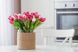 A bouquet of tulips on a white table. In the background, the interior of a white kitchen in the Scandinavian style. The concept of home comfort.The concept of International Women's Day on March 8.