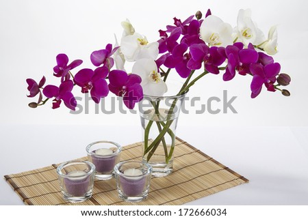 A bouquet of white and purple orchids in a vase. The vase is standing on a place mat made of bamboo.