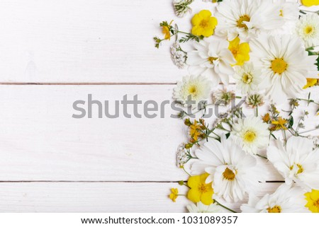 A bouquet of white cosmea, cosmos on white boards. Yellow flowers on handmade wooden table background. Backdrop with copy space, flat lay, top view. Mother's, Valentines, Women's, Wedding Day concept.