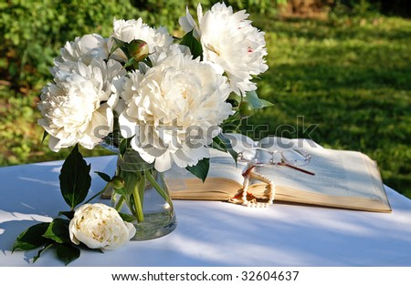 A bouquet of white peony flowers in a glass vase on a garden table in summer evening with an open book, a string of pearls and eyeglasses on blur background