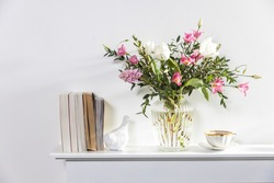 A bouquet of white tulips, pink eustoma, hyacinth, eucalyptus in fluted glass vase on panel of an artificial fireplace. Tea in a cup, faience figurines of a bird and an angel. Empty space.