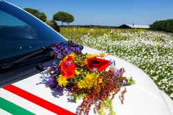 A bouquet of wildflowers on the hood of a car against a flowering meadow. Close-up.