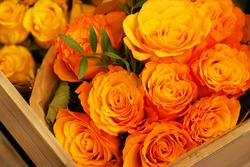 A bouquet of yellow orange roses with a green twig view from above in a wooden box in a flower shop. Rosa.