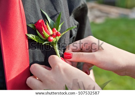A boutonniere flower arrangement being pinned to a shirt for the prom.