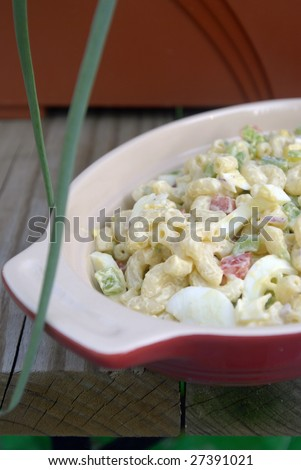 A bowl/container of pasta salad with onions, red and green peppers, and eggs.