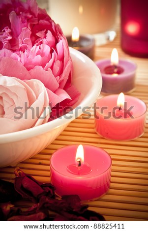 A bowl full of beautiful pink aromatherapy flowers with candles. Spa scene.