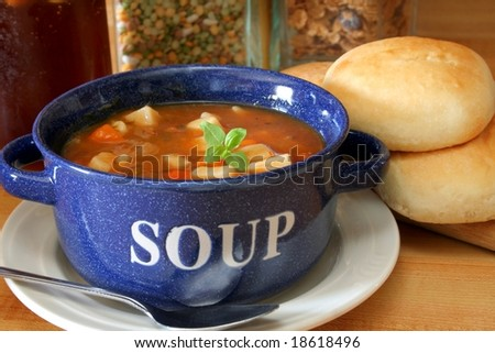 A bowl full of vegetable beef soup and fresh yeast rolls.